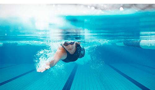 Underwater view of someone swimming laps in a pool for exercise