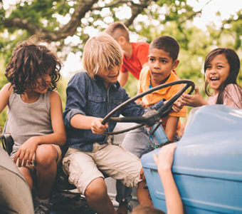 Group of children playing on stationary tractor
