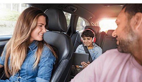 Parents in front of car looking back at child in back who is watching their digital tablet with headphones on