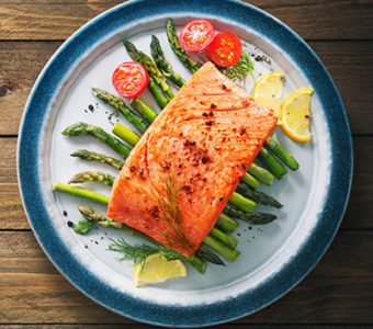 Plate with cooked salmon sitting on top of asparagus