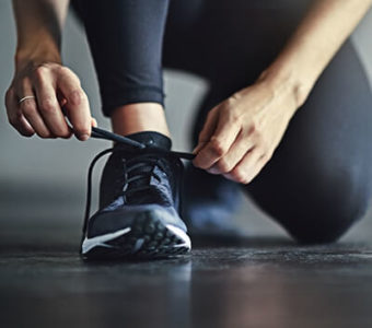 Closeup of someone kneeling on the ground to tie the laces of their athletic shoe