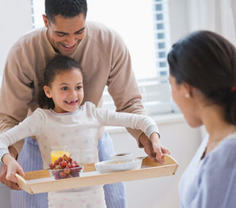 Father and daughter bringing a woman a breakfast in bed on a tray