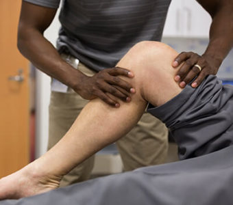Physical therapist assessing a person's injury in their knee