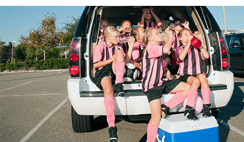 Soccer team sitting in trunk of SUV drinking water and resting