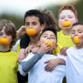 Group of young children holding each other and smiling with orange slices in their mouths