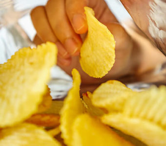 Closeup inside of potato chip bag as a hand pulls out a potato chip