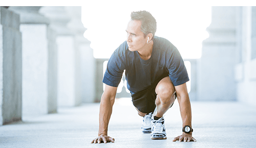 Man stretching legs while on a run outdoors