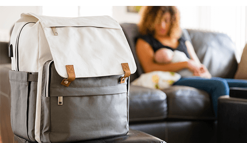 Closeup of diaper bag with mother breastfeeding a baby in the background