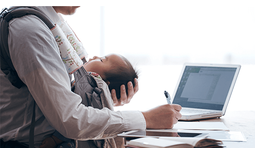 Person holding sleeping baby in carrier while writing on paper near a computer