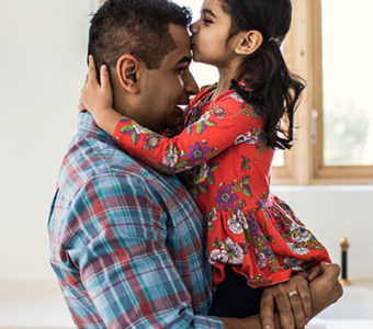 Father holding daughter in arms while she kisses his forehead