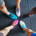 Closeup of a group of people's feet wearing different colored running shoes