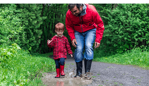 Father and Son Walking in Rain Puddles