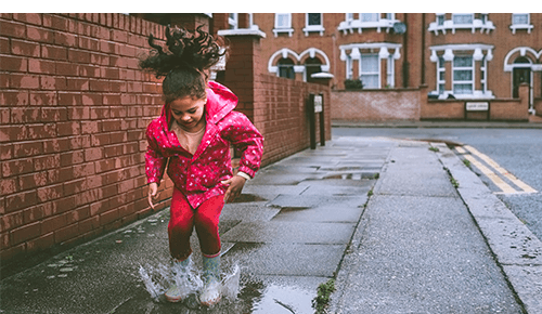Girl Jumping in Rainy Day Puddles
