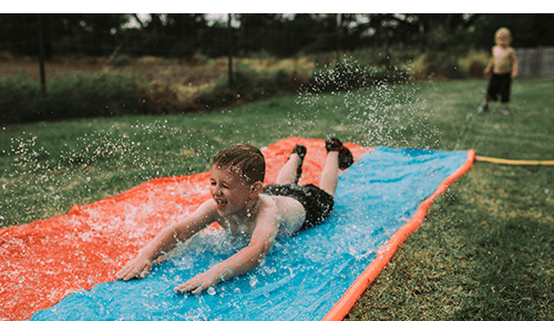Boys Playing on Water Slip and Slide