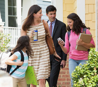 Parents and two children leaving their house in the morning for school and work