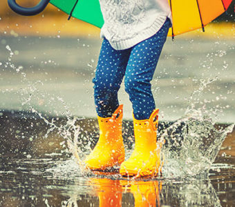 Child playing in rain puddles with rain boots and an umbrella