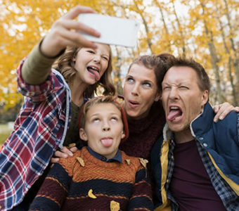 Family outside during the fall making funny faces while taking a picture of themselves