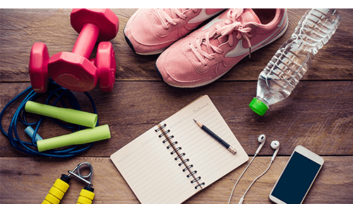 Fitness gear and tech with a notebook and tennis shoes