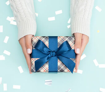 Person holding gift wrapped in blue bow and paper