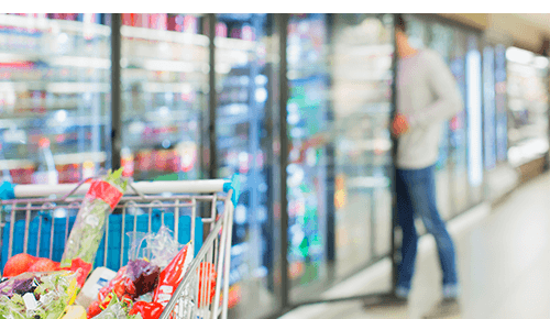 Shopping cart full of food with man looking at freezer aisle food in the background