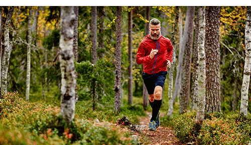 Man trail running in forest