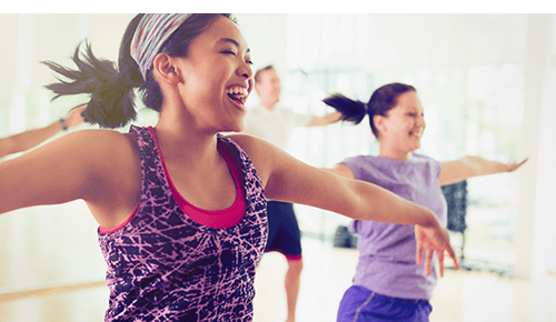 Woman smiling doing cardio dance exercise