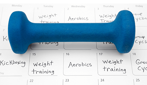 Workout schedule calendar with dumbbell on top