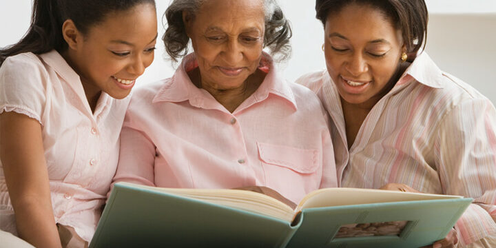 Grandmother and grandchildren looking at book together