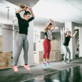 Group performing cardio exercise in gym