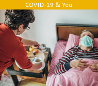 Person bringing food to their loved one sick in bed with a mask on