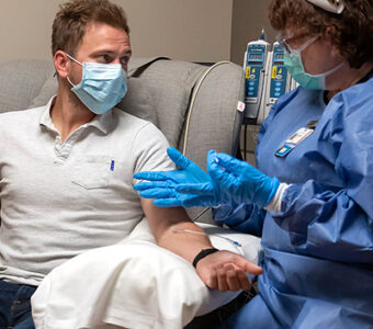 Person wearing a mask receiving infusion therapy