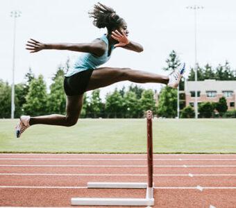 Teen running hurdles on track
