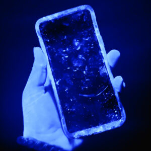 Black light photo of mobile phone showing germs on surface