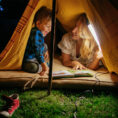 Mother and child reading a book together in a tent set up outside