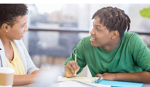 Teenager looking through homework with adult