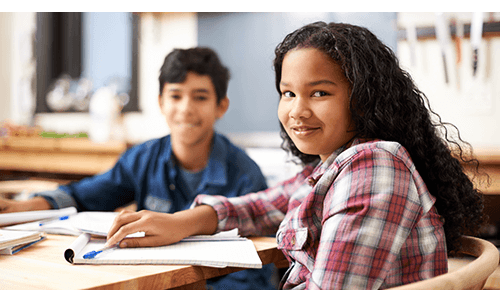 Two middle school aged children working on homework at table