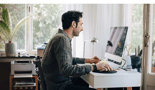 Man working on computer at home desk