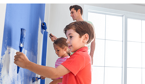 Father and children painting a wall