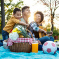 Parents and child sitting outside on a blanket having a picnic