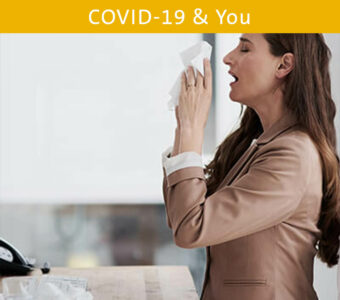 Person sneezing into facial tissue while seated at work desk
