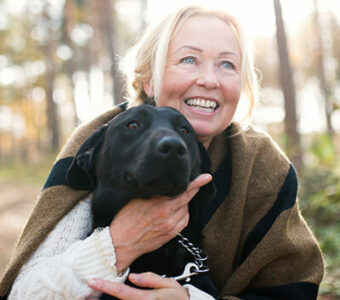 Woman smiling hugging dog outside