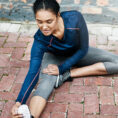 Woman stretching legs on ground before exercise