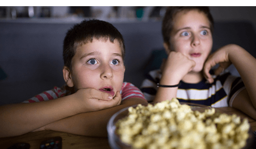 Children watching movie while eating popcorn
