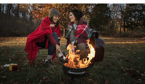 Two people sitting next to campfire roasting marshmallows