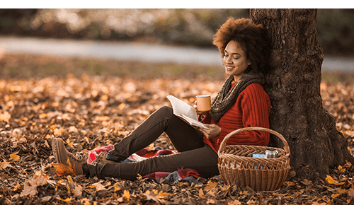 Woman sitting next to tree reading a book
