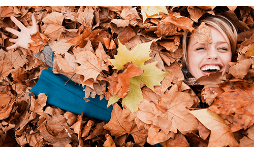 Woman laying in pile of fallen leaves