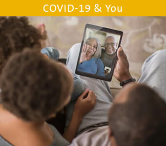 Family talking to grandparents virtually on tablet