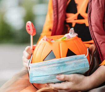 Child holding pumpkin candy basket that has a face mask sitting over it