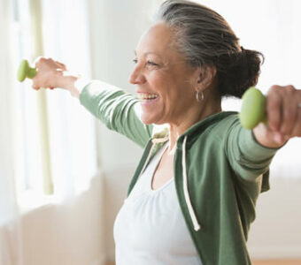 Smiling woman working out with dumbbells