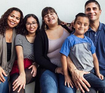 Hispanic family smiling at camera in group photo
